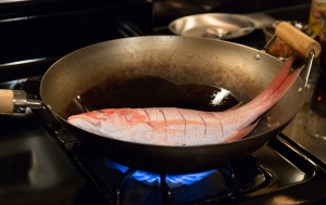 The fish sitting in the wok, frying briefly