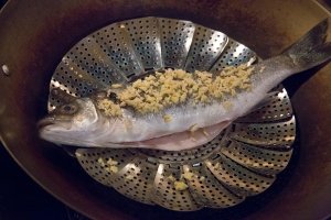 The fish, on the steamer tray, in the wok, over the boiling water