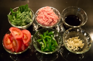 Clockwise, from upper left: basil, ground chicken, soy sauce and fish sauce, chopped garlic, green chiles, and tomatoes